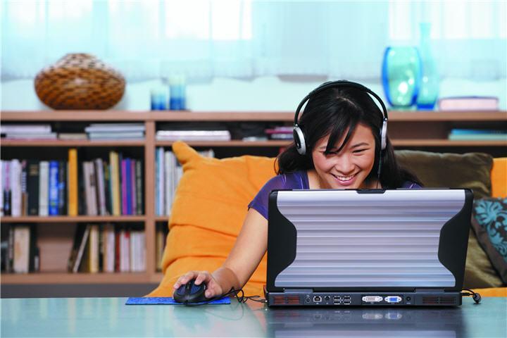 asian woman sitting at a table wearing headphones playing a game on a laptop บทความเรื่อง : สิ่งควรรู้ในการเลือกซื้อคอมพิวเตอร์ (เลือกคอมพิวเตอร์อย่างไรให้ตรงกับการใช้งานมากที่สุด)